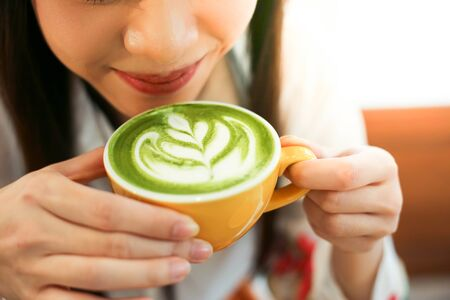 Close up a beautiful woman with Cup of Matcha green tea latte in cafe Reklamní fotografie