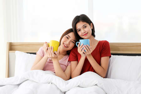 Happy Couple  asia woman enjoy together with drink morning coffee, fresh tea or hot milk in cup on the bed in morning. 版權商用圖片