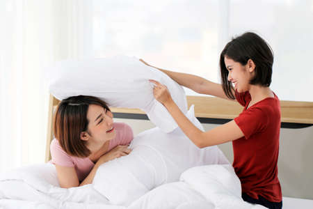 Happy young couple friend beautiful asia women having a pillow fight in their bedroom. 版權商用圖片