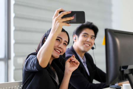 Asia Beautiful woman customer support operator taking a selfie photo of her team  in a call center