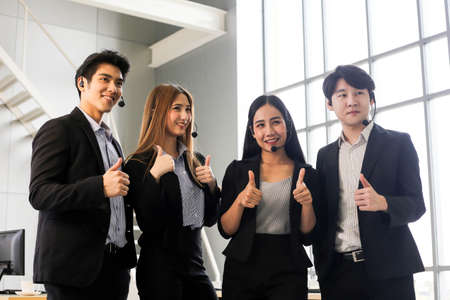 Asia Group of call center workers or Confident business team with headset in office.