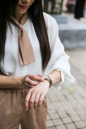 Beautiful woman looking at her watch.