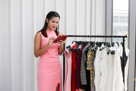 Asian woman beauty blogger or vlogger review  in clothing store,Online influencer girl social media marketing.
