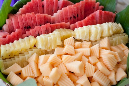 Variety of sliced fruits on banana leaf photo