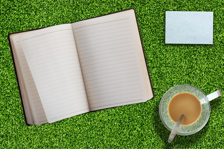 Notebook on Grass With Coffee and short note photo