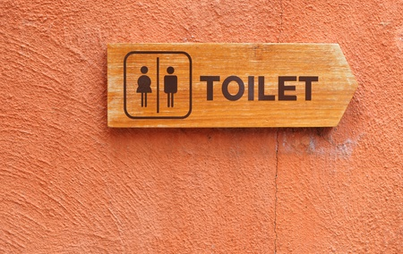 Toilet sign on an orange wall photo