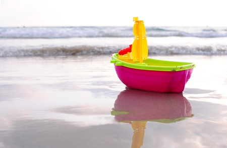 Plastic toy boat on a beach sand Stock Photo