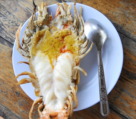 compared: Giant lobster grilled compared size with spoon Stock Photo