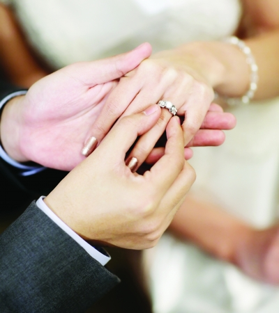Close up on hand of a man put on an engagement ring on the finger of the bride photo