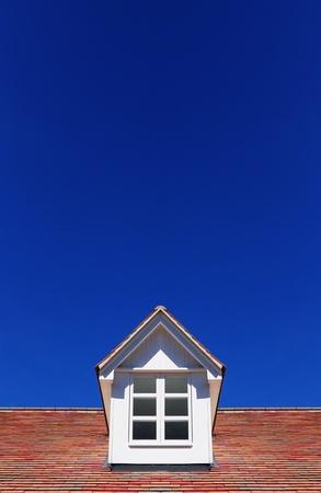 Roof window on blue sky background Stock Photo