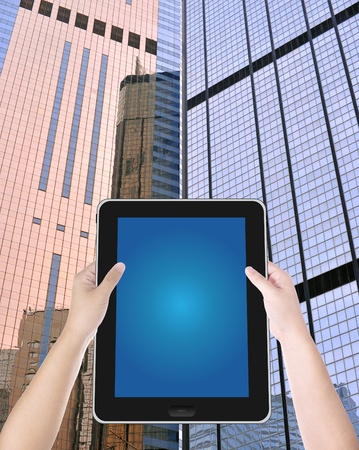 hand hold digital tablet PC with building background photo