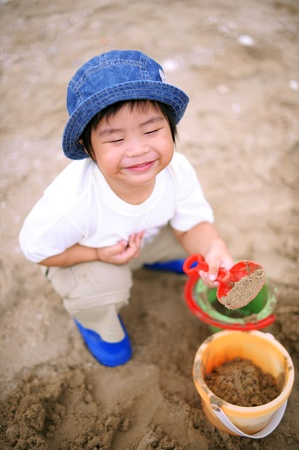chinese hat: Asian kid playing sand in the park