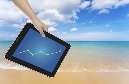 Hand holding digital tablet PC with a nice beach background