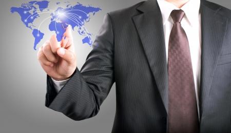 Businessman pointing on world map interface screen Stock Photo - 13601011