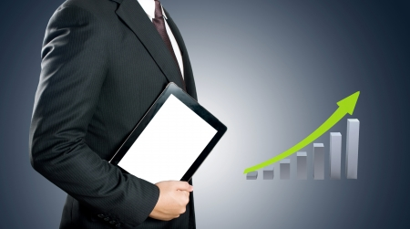 Business man showing tablet PC with green growth graph background photo