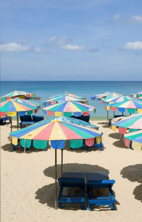 Beach chairs and row of umbrella on the sand beach with cloudy blue sky