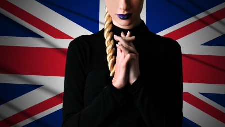 Woman in praying action with UK flag background Stock Photo