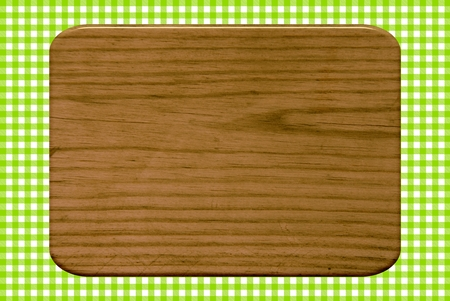 Wooden board on a green tablecloth pattern