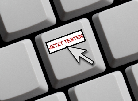 computer language: Computer keyboard with mouse arrow showing test it in German language