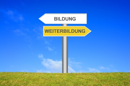 further education: Signpost sign with blue sky and green grass showing training or further education in german language Stock Photo