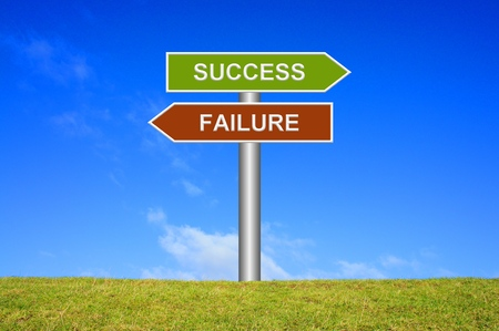 Signpost sign with blue sky and green grass showing success or failure Stock Photo
