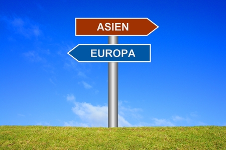 groundbreaking: Signpost is showing Europe or Asia in front of blue sky and green grass