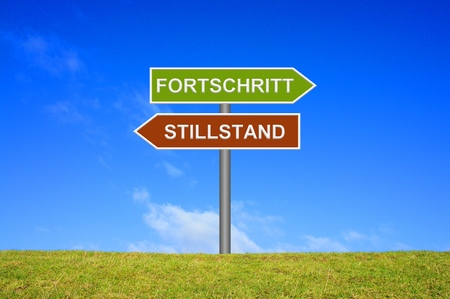 groundbreaking: Street Sign showing progress or standstill in german language in front of blue sky on green grass Stock Photo