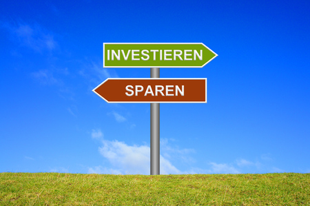 avarice: Street Sign showing investing saving in german language in front of blue sky on green grass Stock Photo