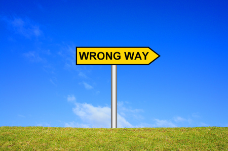 fallacy: Street Sign showing wrong way in front of blue sky on green grass
