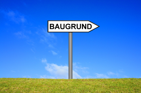 grass plot: Street Sign showing Plot in german language in front of blue sky on green grass