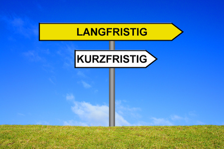 long term goal: Street Sign showing short term or long term in german language  in front of blue sky on green grass