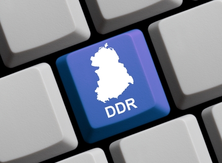 east berlin: Outline of GDR on a blue computer Keyboard with word in in german language