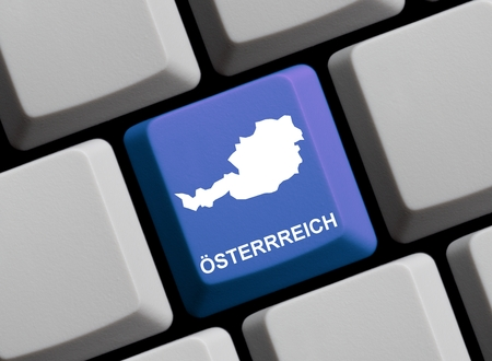 computer language: Outline of Austria on a blue computer Keyboard with word in in german language Stock Photo