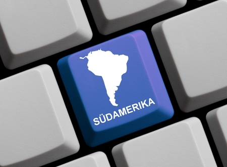 south america: Outline of South America on a blue computer Keyboard with word in in german language