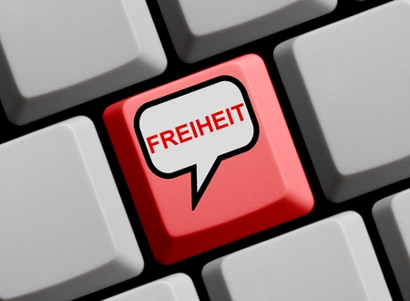 computer language: Red Computer Keyboard with speech bubble showing Freedom in german language