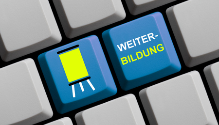 further education: Blue computer keyboard with symbol showing Further Education in german language Stock Photo