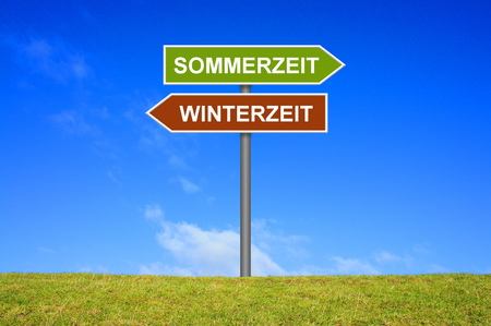 Signpost outside is showing Summer Time and Winter Time in german language in german language Stock Photo