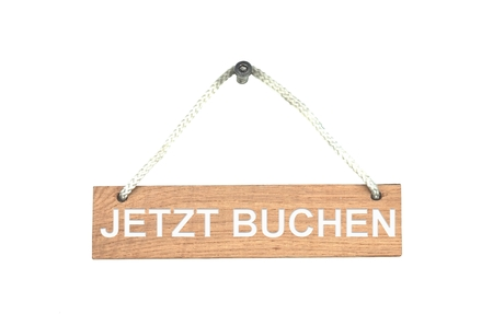 Wooden sign hanging on rope showing Book now in german language Stock Photo