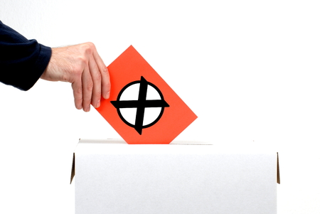 Hand inserting Envelope into ballot box