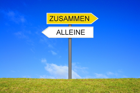 Signpost outside is showing Alone or together in german language Imagens