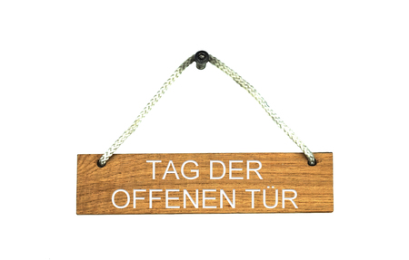 Old brown isolated wooden sign with rope showing Open Day in german language Standard-Bild - 107319446
