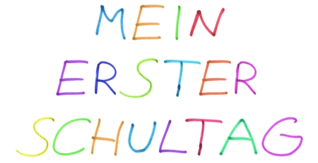 My first day at school in german language - Colorful handwritten text on white background