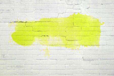 Biały ceglany mur z pustym żółtym obrazem lub graffiti