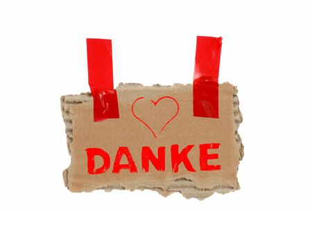 Brown cardboard with red adhesive tape showing Thank You in german language