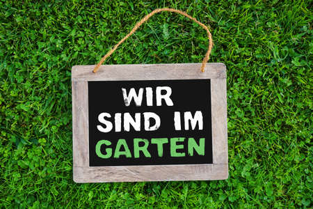 We are in the Garden in german language on wooden chalkboard in green grass