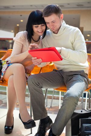 love story of young couple in shopping mall shopping by internet
