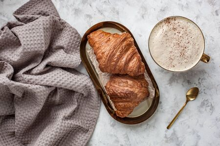 breakfast with two croissants and cappuccino on a grey stone table Archivio Fotografico