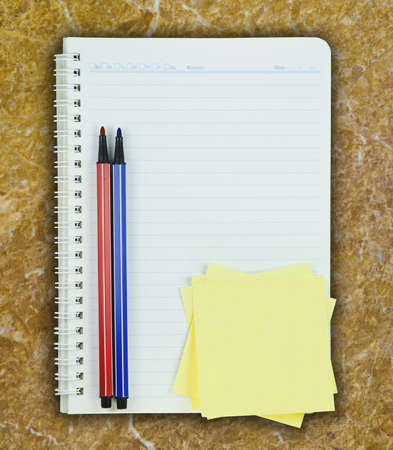 Book, colorful pen and post it on marble background photo