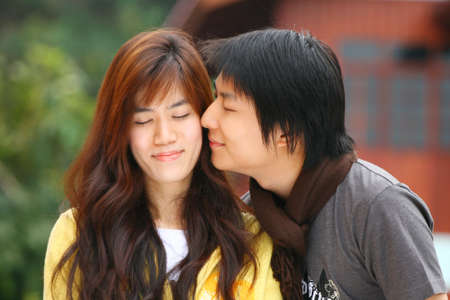 An Asian Man kiss his girlfriend photo