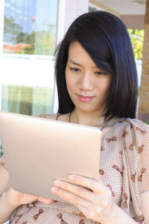 Beautiful asian woman using tablet computer photo